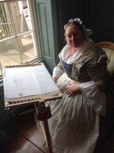 Alison Larkin stitching as Elizabeth Cook in 18th century costume.
